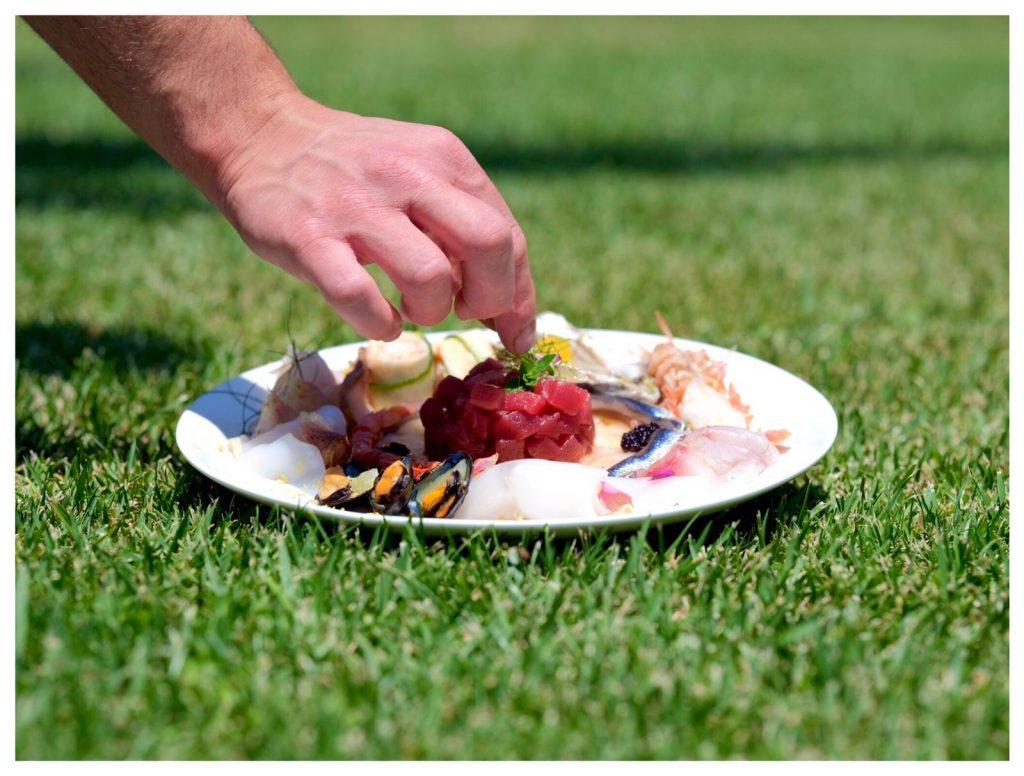 Tartar di carne su piatto bianco su prato inglese con mano dello chef che posa del basilico